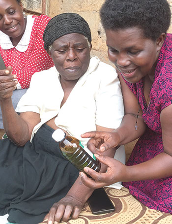 Rose Nabatanzi (R) showing a morphine bottle to Janet Nabadda