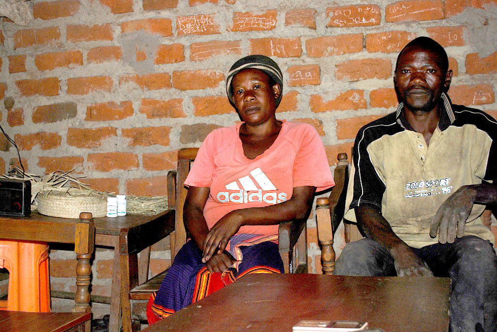 The couple in sit inside the new house,on the table are their ARVs. They adhere to drugs by reminding each other since they are all HIV positive.